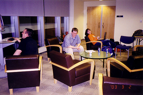 The lobby at the first Animarathon. Two people sit in comfy chairs. Another uses the tangerine orange lounge CRT all in one Computer.